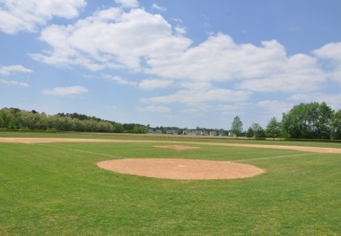 green field and orange dirt baseball field